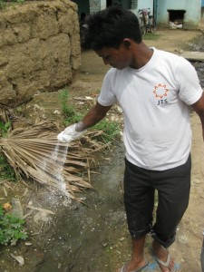 A Sujata Academy teacher spraying disinfectant along the waterway